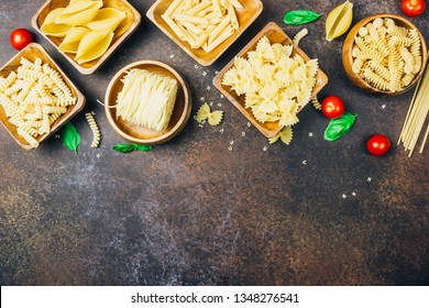 Various pasta on wooden bowls over dark background. Top view with copy space