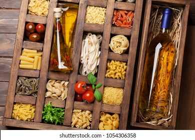 Various pasta in wooden box and white wine bottle. Cooking concept. Top view