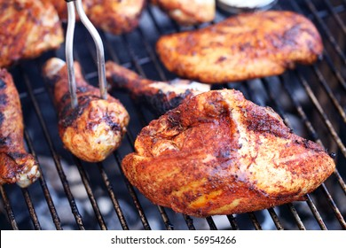 various pieces of chicken cooking on grill