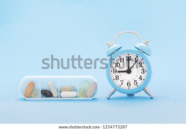 Various pills and capsules in organizer and clock on blue background. Time to get healthy, daily vitamins and supplements dosage routine concept.