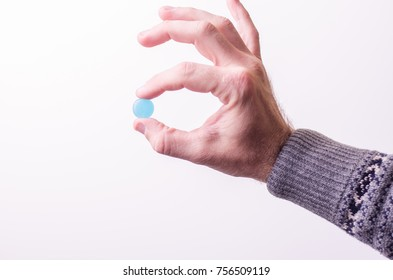various pills, thermometer on a blue background
