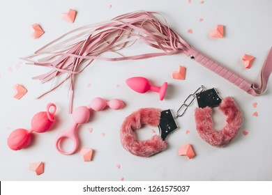 Various pink sex toys are arranged on a white background with pink hearts. Romantic background for goods from a sex shop or Valentine's Day