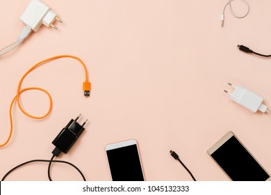 Various plugs and cables and smartphones on pastel background. Flatlay frame, technology or connection concept, copyspace