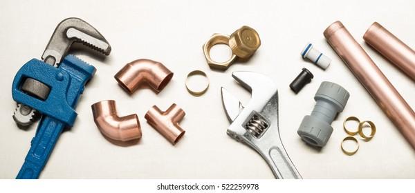 Verschiedene Klempnerwerkzeuge und Klempnerwerkstoffe, einschließlich Kupferrohr, Ellbogengelenk, Schraubenschlüssel und Spanner. Aufnahme auf hellrostfreiem Hintergrund.