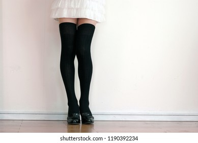 Various poses of beautiful legs of black knee high socks on micro miniskirt.