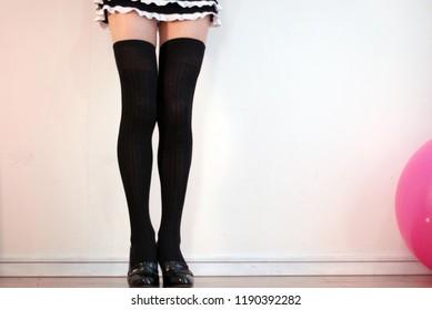 Various poses of beautiful legs of black knee high socks on micro miniskirt.