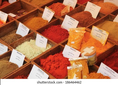 Various powdered Spices on a market stand labeled in French.