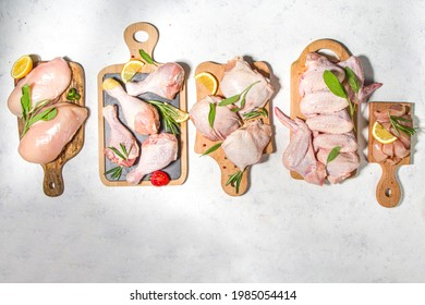 Various raw chicken meat portions. Set of uncooked chicken fillet, thigh, wings, strips and legs on white cooking table background with spices