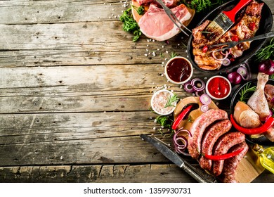 Various raw meat ready for grill and bbq, with vegetables, greens, sauces kitchen grilling utensils. Chicken legs, pork steaks, sausages, beef ribs with herbs, rustic wooden background copy space