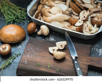 Various raw mushrooms - King trumpet mushroom (Eringi), white and brown mushrooms, Portobello  on a dark table with a cutting board and herbs. Selective focus.