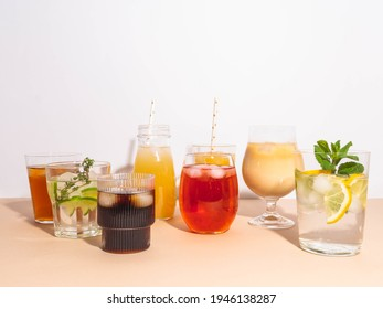 Various refreshing non-alcoholic drinks in glasses with ice. Different juice, homemade lemonade, iced coffee, iced fruit tea and smoothies on beige background. Copy space. Front view