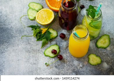 Various refreshments drinks - detox cucumber water, cherry juice and orange juice on stone table. Top view flat lay with copy space for your text.