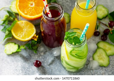 Various refreshments drinks - detox cucumber water, cherry juice and orange juice on stone table.