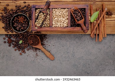 Various of roasted coffee beans in wooden box with manual coffee grinder setup on shabby wooden background.