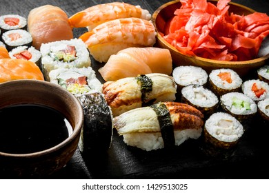 Various rolls, sushi and maki on a stone Board with soy sauce and ginger. On dark rustic background