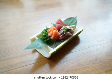 Various sashimi set of fresh sliced raw fish with tuna (akami), salmon and horse mackerel (aji), served with wasabi and shredded radish, Japanese traditional food.