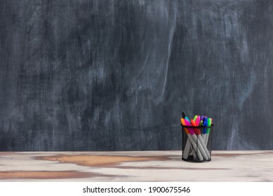 Various school and stationary supplies on a homemade rustic table in front f a blackboard