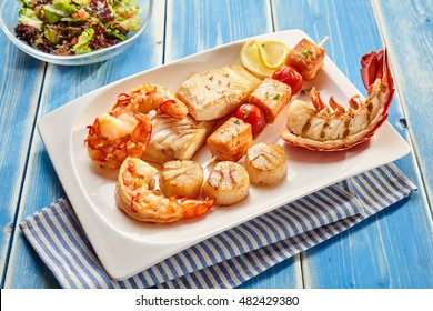 Various seafood appetizers consisting of lobster, crab cakes, fish meat and shrimp on plate with striped napkin beside salads