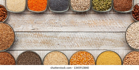 Various seeds and grains in bowls, frame an old white wooden board table - top view, copy space