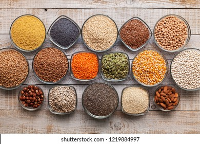 Various seeds, grains and nuts on old table, healthy diverse diet concept, top view