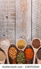 Various seeds and grains in wooden spoons on battered wooden surface - top view, close up, copy space