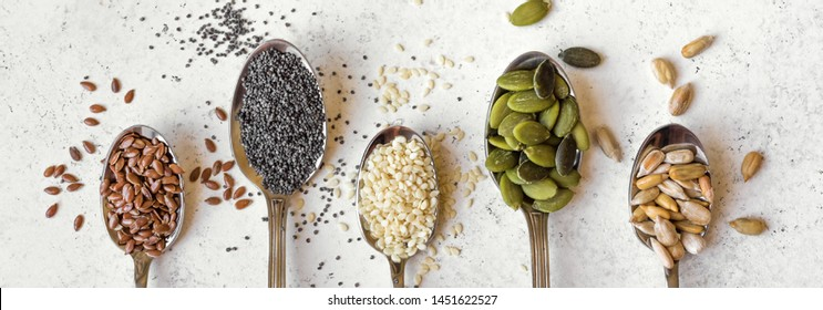 Various Seeds on white background. Assortment, set of seeds on spoons, healthy food ingredients, superfood, top view, banner.