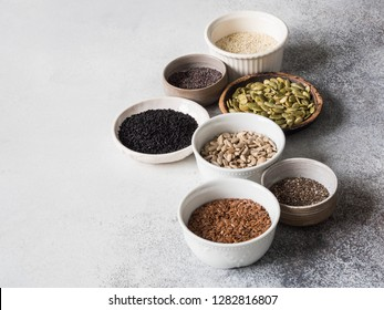 Various seeds - sesame, flax seed, sunflower seeds, pumpkin seed, poppy, chia in bowls on a gray background. Copy space.