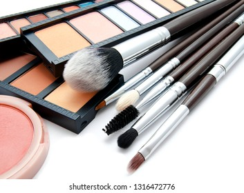 Various set of professional makeup brushes and palette of colourful eye shadows isolated over white background