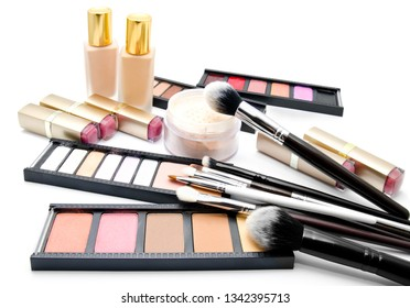 Various set of professional makeup brushes and cosmetics and palette of colourful eye shadows isolated over white background