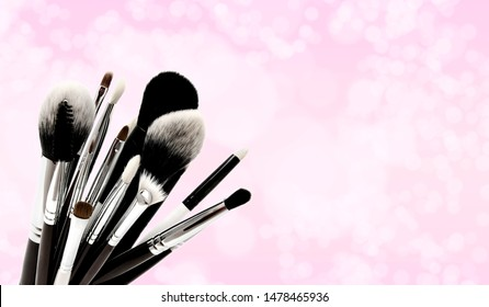 Various set of professional makeup brushes isolated over pink background