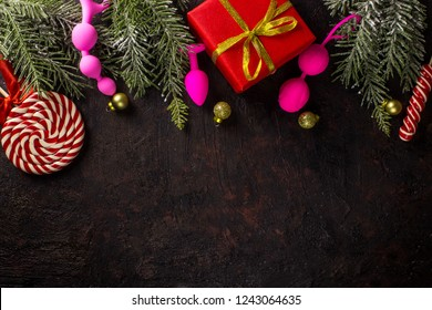 Various sex toys (anal balls, vibrator, fur handcuffs and others), christmas balls and candy. New Year or Christmas festive background for Sex shop