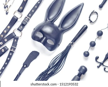Various sex toys (anal balls, vibrator, leather harness, lash, rabbit mask and others) are on a white background.