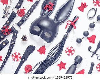 Various sex toys (anal balls, vibrator, leather harness, lash, rabbit mask and others) are on a white background. Nearby are red felt Christmas decorations. Christmas composition for sex shop.