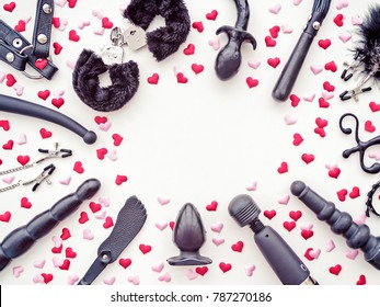 Various sex toys are arranged on a white background with pink and red hearts. Romantic background for goods from a sex shop or Valentine's Day