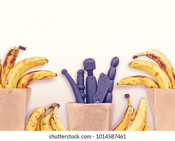Various sex toys (dildo, wand-massager, slapstick and others) are in a paper shopping bag. To the right and left are ripe bananas in bags. Light background (for sex shops or grocery stores)