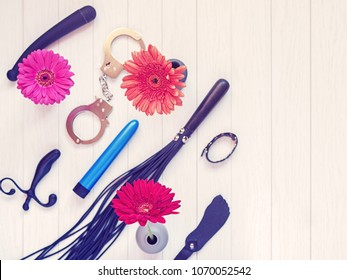 Various sex toys and gerbera flowers in vases are on a light wooden background. Image for sex shop advertising, promotion on the Internet, discounts and sales, email newsletters and other