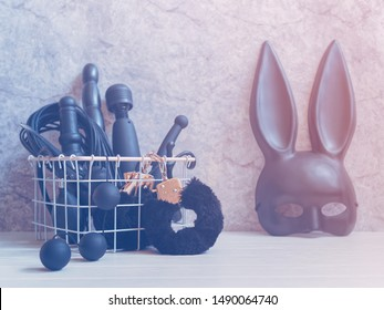Various sex toys (handcuffs, dildo, vibrator, balls) are in a white metal basket. Nearby is a black mask with rabbit ears. Gray background with cracks and scuffs. Minimal composition.