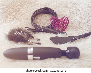 Various sex toys (leather whip, nipple clamps, wand massager, slapstick) and a red wicker heart are on a fur background. Image in retro style to Valentine's Day or to any romantic event