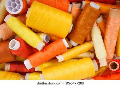 Various shades of yellow sewing thread spools