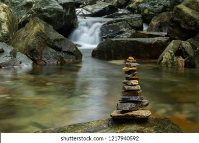 Various shaped stacked Zen stones against a waterfall background