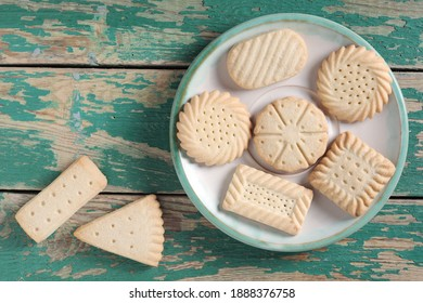Various shortbread cookies on a plate on old green wooden background, top view