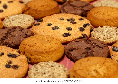Various shortbread and oatmeal cookies with flakes and raisins on a wooden background.