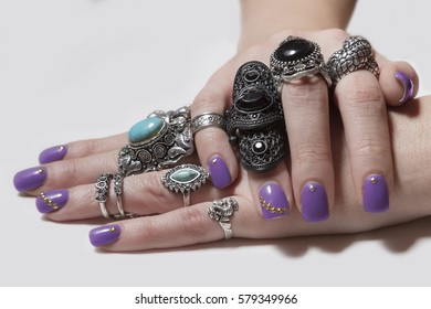 Various silver rock rings with nice manicured fingernails. Soft focus