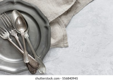 Various silverware on a pewter plate and gray flax napkin are on the background of gray concrete surface, with copy-space