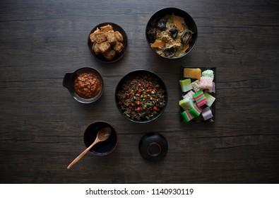Various Singapore Peranakan Food Flat Lay. Peranakan Food on Wooden Table. Cap Chye, Peranakan Fried Rice, Ngoh Hiang, Wooden Spoon, Black Bowls. Nonya Food, Baba Food.