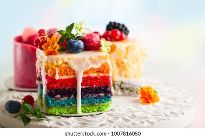 Various slices of cakes on a white tray: rainbow cake, raspberry cake and almond cake. Sweets decorated with fresh berries and flowers for holiday