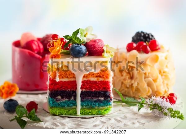 Verschillende plakjes cakes op een wit dienblad: regenboogcake, frambozencake en amandelcake. Snoepjes versierd met verse bessen en bloemen voor vakantie