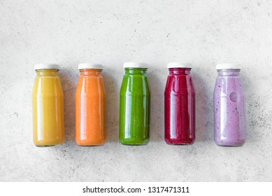 Various smoothies or juices in bottles, healthy diet detox vegan clean food concept, top view, copy space. Colourful smoothies on white background.