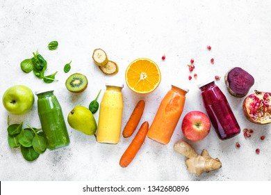 Various smoothies or juices in bottles and ingredients on white, healthy diet raw detox vegan clean food concept, top view, copy space.