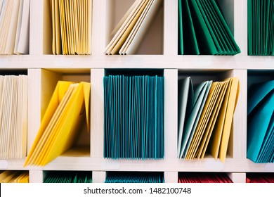 Various sort mail envelopes arranged on a shelf by color and type categories.  Front view.